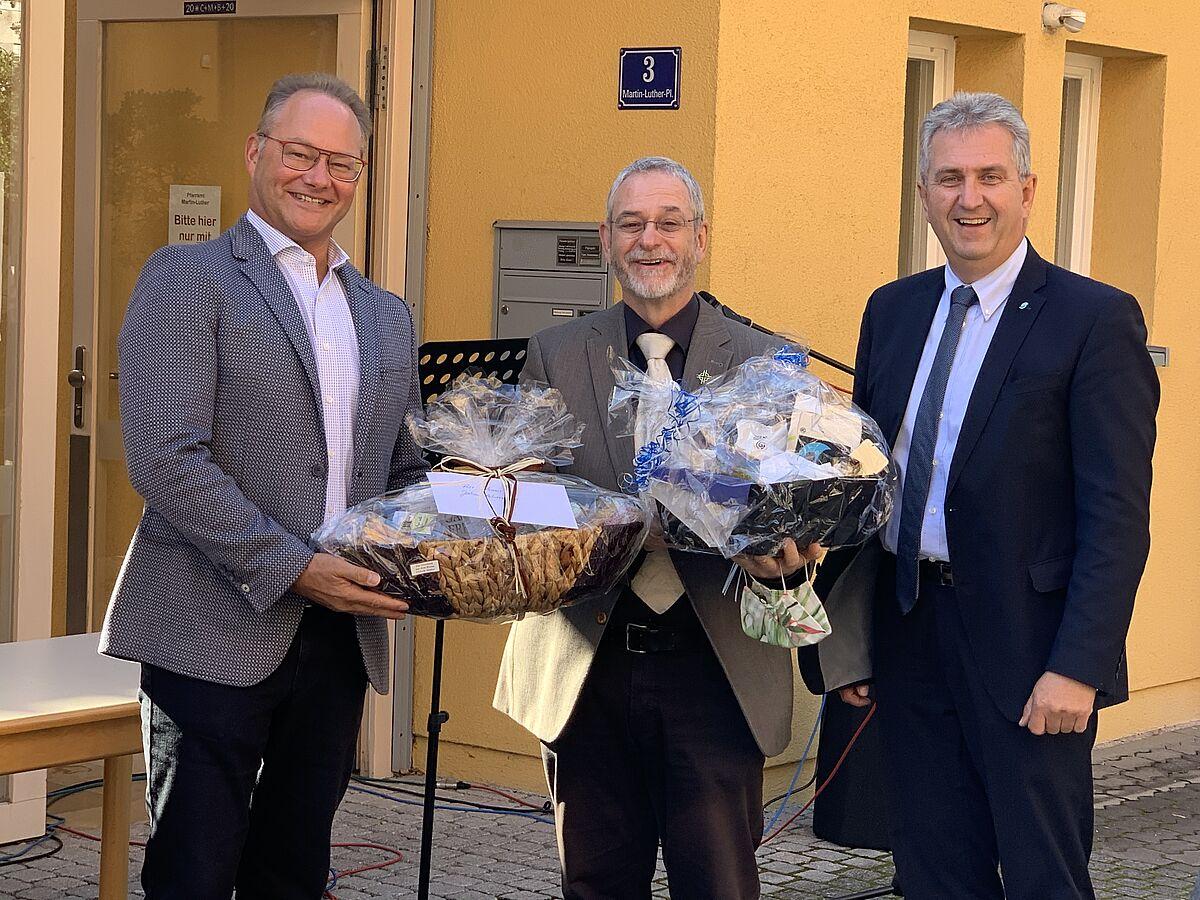 Klaus Heinrich (Vorstand des Kommunalbetrieb Stein) und Erster Bürgermeister Kurt Krömer überreich Pfarrer Jochen Ackermann Geschenke